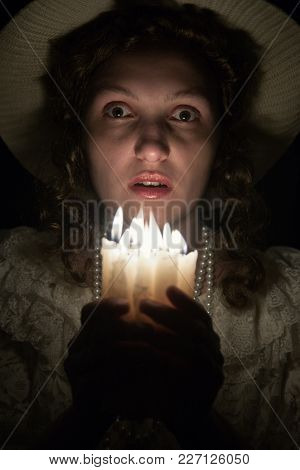 Scared Young Woman With Candles In The Dark Looking At Camera