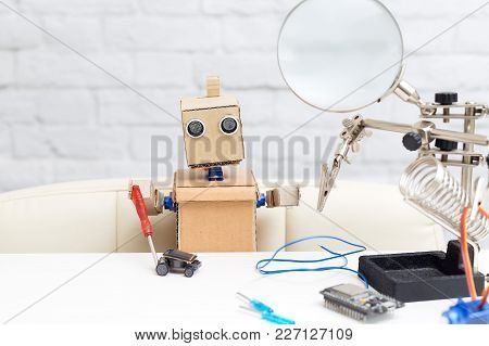 The Robot Holds A Screwdriver In His Hand And Collects The Machine On A Solar Battery. Artificial In