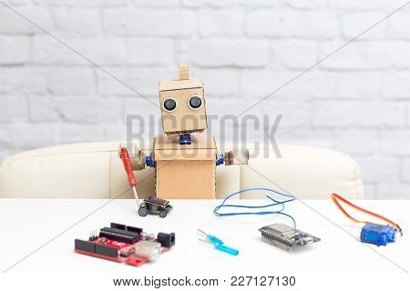 The Robot Holds A Screwdriver In His Hand And Collects The Machine On A Solar Battery. Future