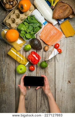 Online Shopiing Concept - Hands Holding Phone Making An Order. Grocery Shopping Concept. Balanced Di