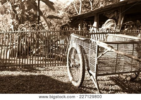 Sepia Old-fashioned Image Of Old Pushcart On Lawn In Front Of Old Bamboo Fence And Farm Shed
