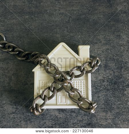 Small White House And A Decorative Chain On A Dark Background. Concept  -  Risks, Lose Property,  Se