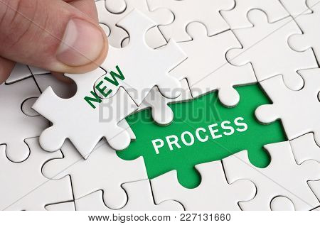 The Human Hand Fills The Last Missing Elements Of The Surface From The Jigsaw Puzzle. Image With Wor