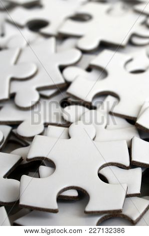 Close-up Of A Pile Of Uncompleted Elements Of A White Puzzle. A Huge Number Of Rectangular Pieces Fr