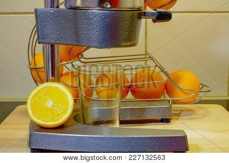 Preparing Fresh Orange Juice Squeezed With A Mechanical Juicer On A Natural Kitchen Background