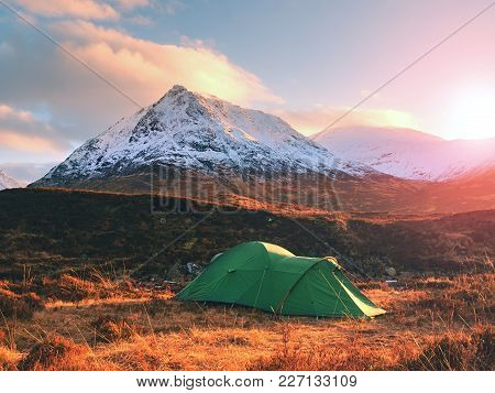 Green Tent And Snowy Mountain Peak. Higland In Scotland An Marvelous Sunny Winter Day. Dry Grass And