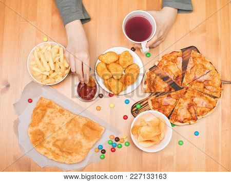 Fast Food Junk Food Concept. Teen Boy Eating Nuggets, Pizza, Chips And Other Fast Food.