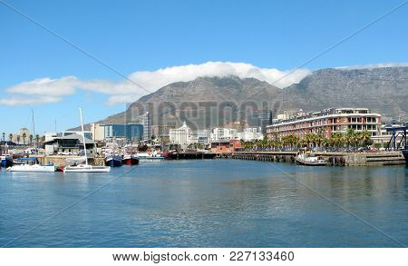 The Victoria And Alfred Waterfront, With Calm Blue Water In The Fore Ground And Table Mountain In Th