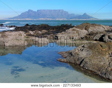 The Cool, Calm Water Of The Atlantic Ocean, With Huge Boulders In The Fore Ground And Table Mountain