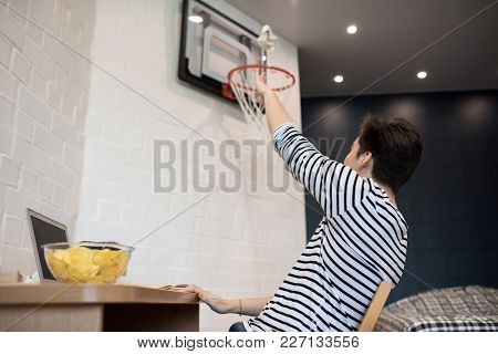 Back View Portrait Of Young Man Throwing Crumpled  Paper Ball In Basketball Ring In His Room, Copy S