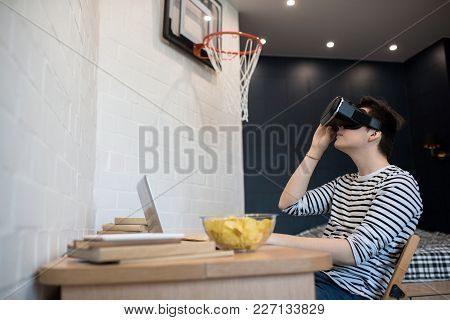 Side View Portrait Of Teenage Boy Using Vr While Sitting At Desk In His Room And Playing Video Games