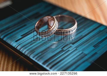 Luxury Pair Of Wedding Golden Rings On A Smartphone. Selective Focus