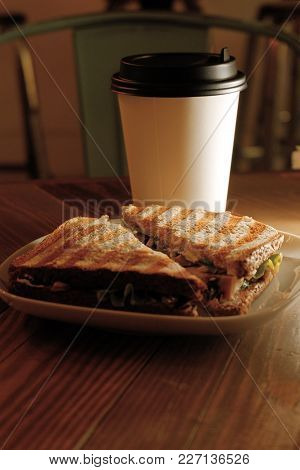 Cup Of Take Away Coffee And Sandwich On Table Half Lit