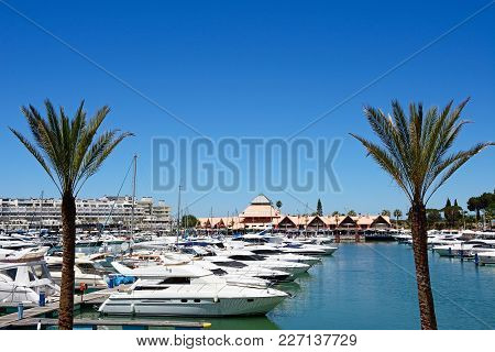 Vilamoura, Portugal - June 6, 2017 - View Of Yachts In The Marina With Buildings To The Rear And Peo