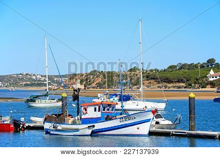 Alvor, Portugal - June 7, 2017 - Fishing Boats And Yachts Moored In The Estuary With People Going Ab