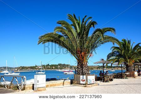 Alvor, Portugal - June 7, 2017 - Tourists Relaxing At A Pavement Cafe Along The Promenade With Views