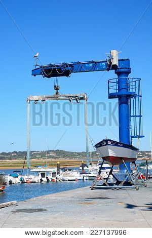 Alvor, Portugal - June 7, 2017 - Fishing Boat In Dry Dock With A Crane To The Rear, Alvor, Algarve,