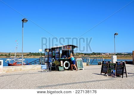 Alvor, Portugal - June 7, 2017 - Boat Trips Booking Office Along The Waterfront With Views Across Th