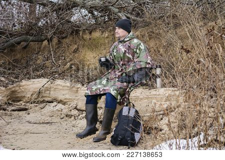 Young Man Walking On Frozen Beach In A Military Raincoat Drinks Hot Tea With Thermos