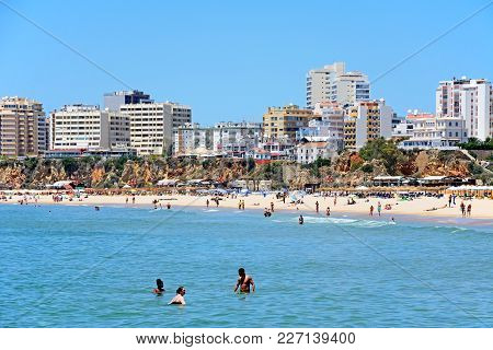 Portimao, Portugal - June 7, 2017 - Tourists Relaxing In The Sea And On The Beach With Apartments An