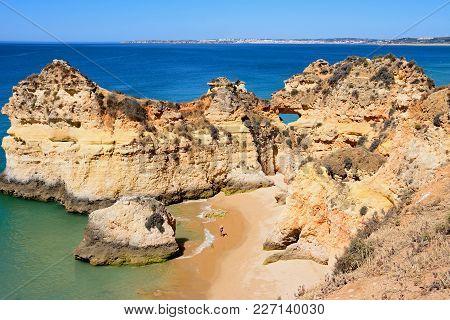 Elevated View Of The Rocky Coastline With Tourists Relaxing On The Sandy Beach, Praia Da Rocha, Alga