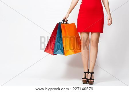 Slender Long Female Legs In Black Sandals, Caucasian Woman In Red Dress Holding Three Multi Colored