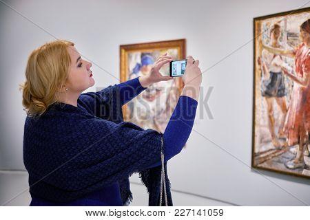 MOSCOW, RUSSIA - OCT 28, 2017: Woman (MR) in Museum of Russian Impressionism takes picture of painting by M.Shemyakin Pioneers on Rest.