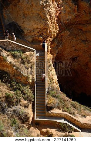 Ponta Da Piedade - June 8 2017 - Elevated View Of The Rugged Coastline With Tourists On The Steps In