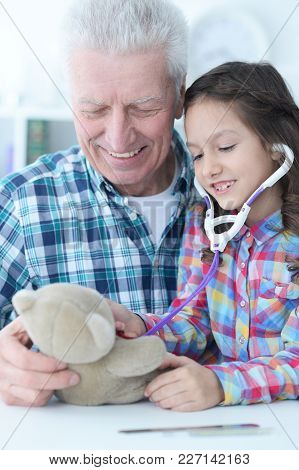 Cute Little Girl Playing Nurse, Inspecting Teddy Bear With Stethoscope