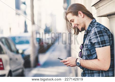 Young Fashionable Man Using A Smart Phone While Waiting For Someone Outside On A Street