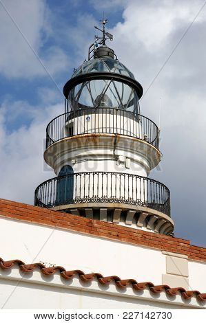 Old White Lighthouse On The Sea Coast Of Spain With Round Metal Railings