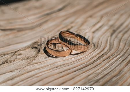 Pair Of Wedding Golden Rings On The Yellow Wooden Rustic Background.