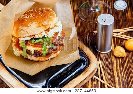 Delicious Hamburger On Wooden Table. Fast Food