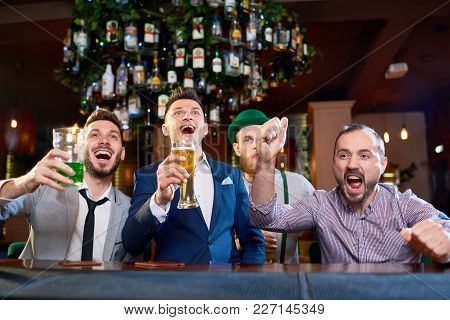 Group Of Bearded Men Celebrating Victory Of Their Favorite Football Team While Sitting At Bar Counte