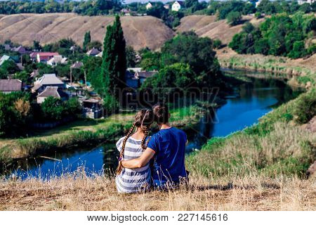 Young Loving Couple Sitting In Hug On The Top Of A Hill With Wonderful View Of The River, Harmony Co