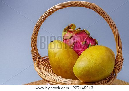 Tropical  Ripe Fruit Mango And Dragon Fruit In A Basket Against Wooden Board, On Gray Background.