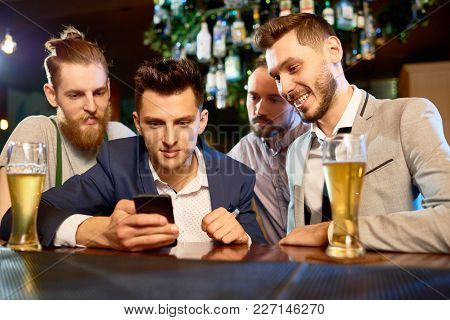 Group Of Bearded Colleagues Gathered Together In Pub After Hard Working Day, Drinking Beer And Watch