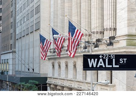 Wall Street Sign With New York Stock Exchange In Background  In Manhattan, New York.