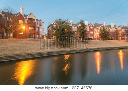 Blurred Riverside Apartment Building Complex Reflection At Blue Hour