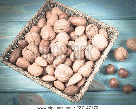 Different Types Of Nuts In A Shell On A Wooden Background.