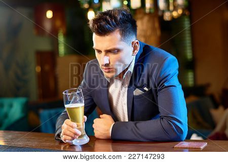 Waist-up Portrait Of Handsome Young Businessman Sitting At Bar Counter With Beer Glass In Hand While