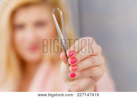 Woman In Bathroom Showing Tweezers For Eyebrows Depilating, Plucking Eyebrows. Focus On Tweezer