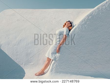 Barefooted Woman With Hat Relaxing Next To The White Walls In Beautiful Village Oia. Lifestyle Conce