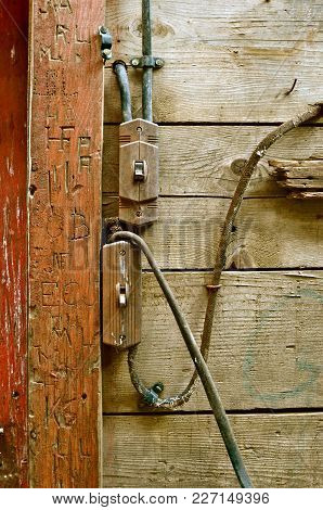 Old Electrical Wiring Is A Fire Hazard In An Old Barn Building Surrounded Bt Carved Initials In The