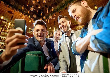 Smiling Bearded Friends Taking Selfie With Help Of Smartphone While Having Long-awaited Gathering In
