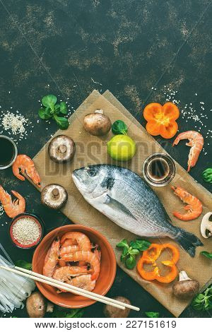 Raw Fish ,shrimp,mushrooms With Spices And Herbs On A Dark Background . Top View, Copy Space