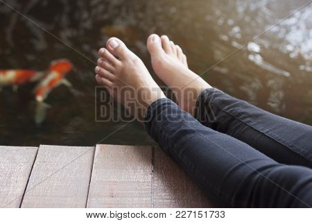 Female Legs Wearing Black Pants On Wooden Floor And Water With Fish For Background.