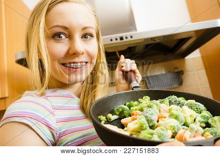 Woman In Kitchen Cooking Stir Fry Frozen Vegetables On Pan And Tasting. Girl Frying Making Delicious