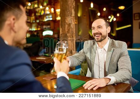 Cheerful Business Partners Wearing Suits Sitting At Cafe Table And Clinking Beer Glasses Together Af