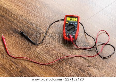 Multimeter Measuring Device Electric Tool For Measurement Of Voltage Lying On Wooden Floor Backgroun